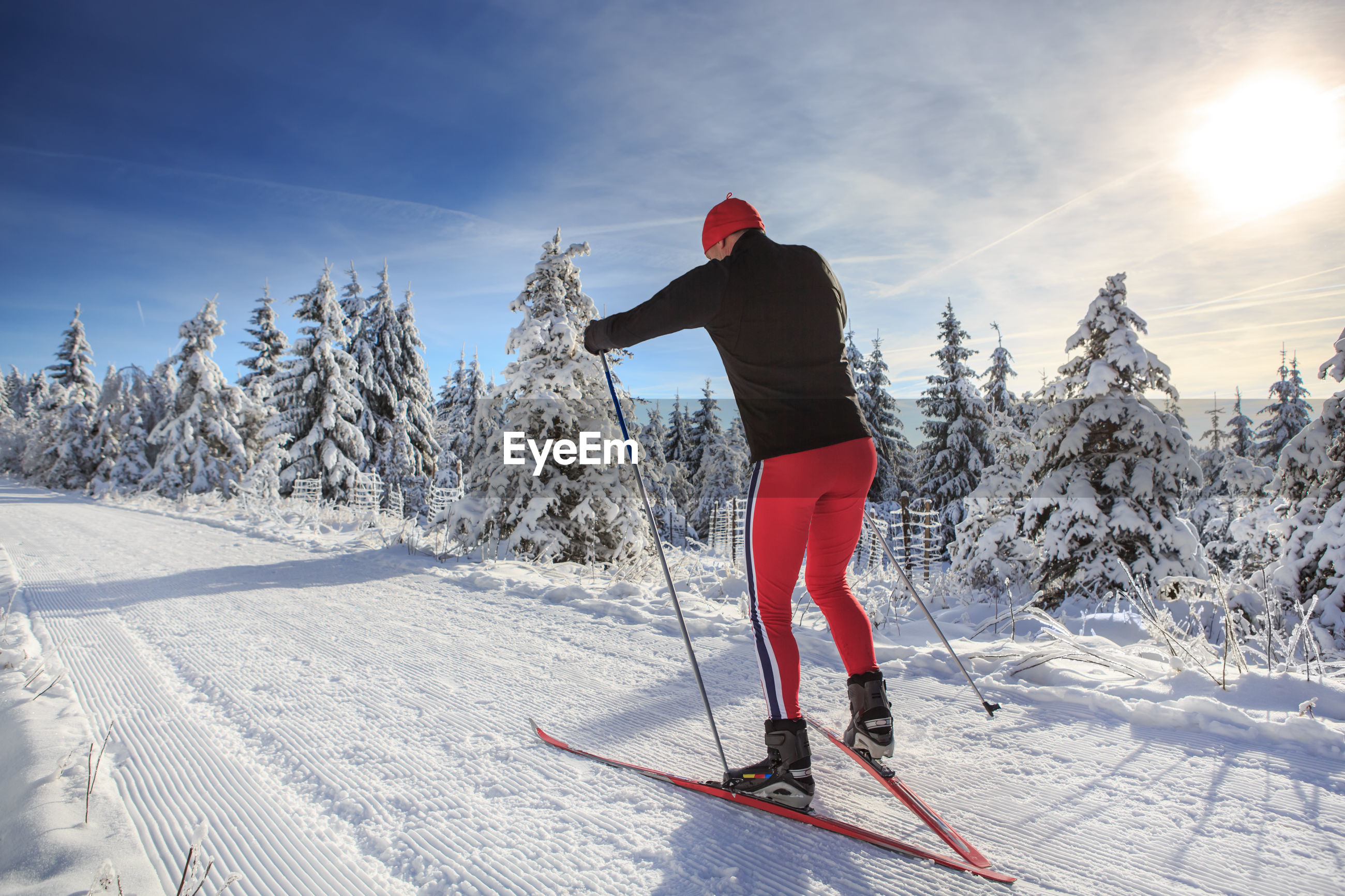 Man skiing on snow covered field against sky