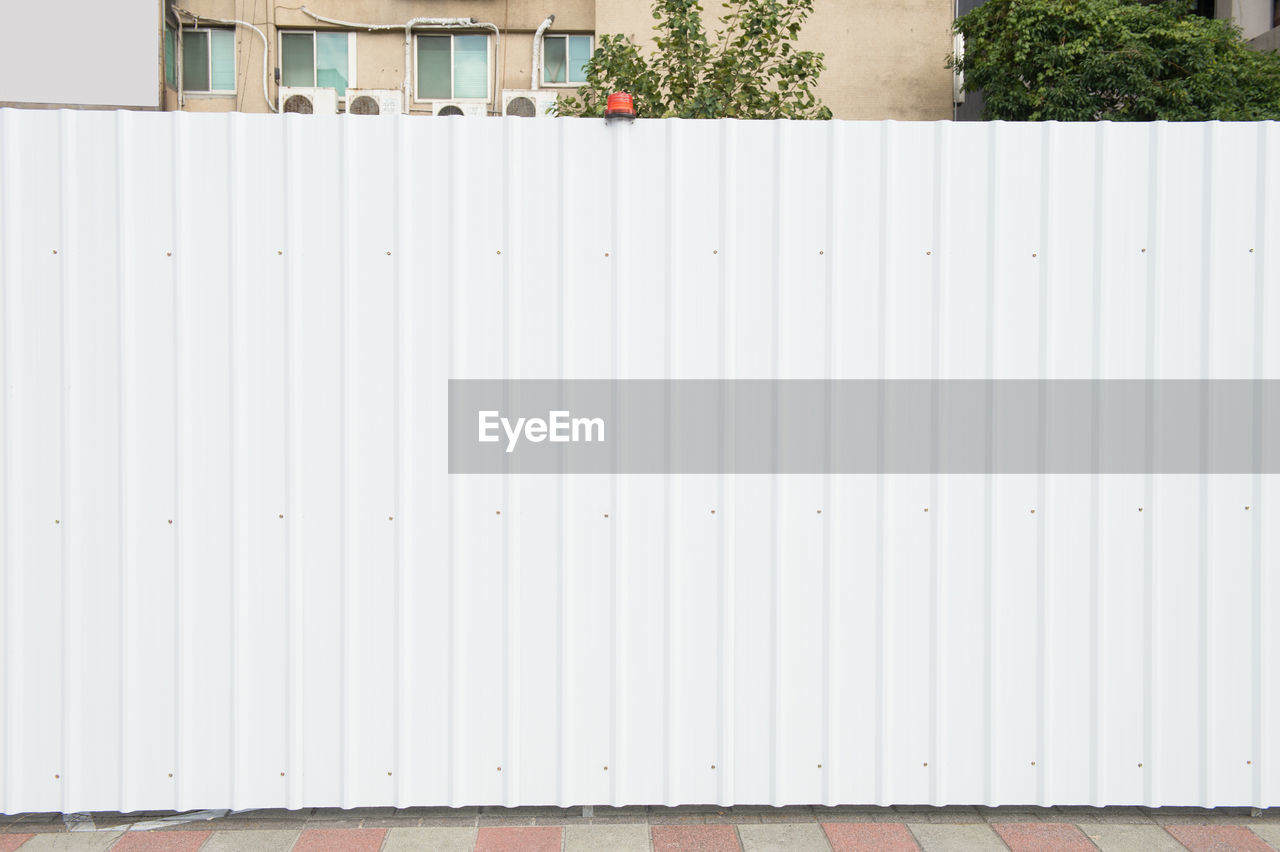 built structure, architecture, building exterior, day, white color, wall - building feature, pattern, no people, metal, outdoors, building, security, iron, protection, safety, nature, wall, closed, corrugated iron, plant, corrugated