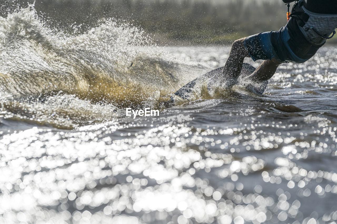 LOW SECTION OF MAN SPLASHING WATER ON SEA