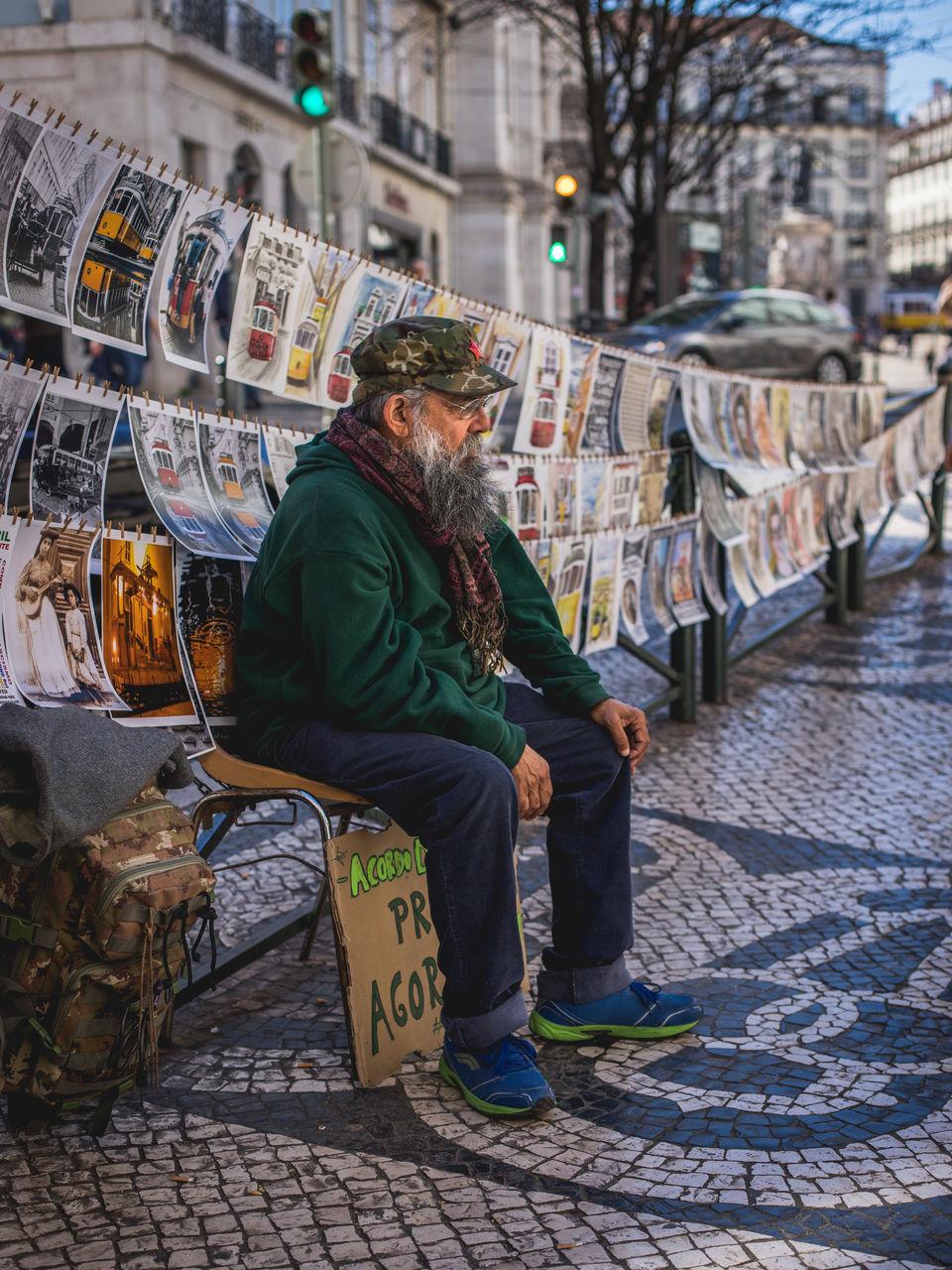 FULL LENGTH OF MAN SITTING ON FOOTPATH AT STREET MARKET