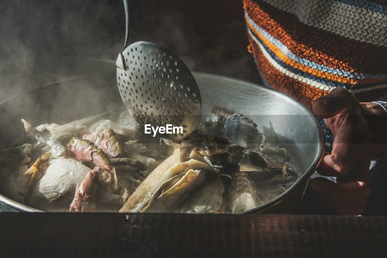 Full frame shot of man holding pan with cooked fish