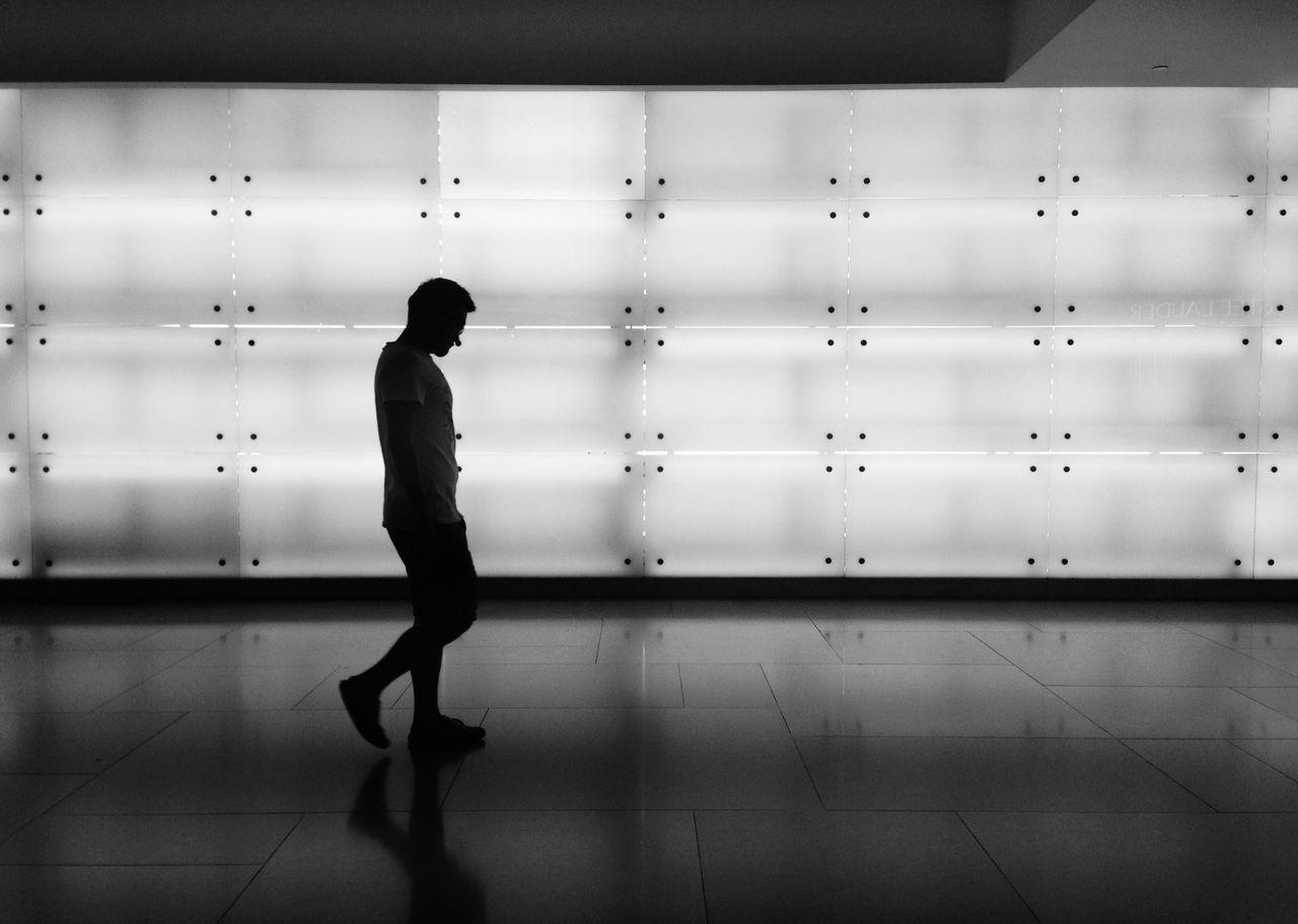 Walking Man Against Illuminated Wall