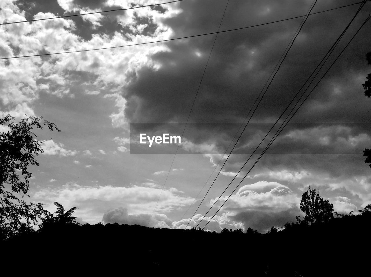 Low angle view of power lines over silhouette trees against cloudy sky