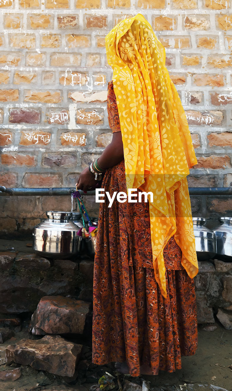 Rear View Of Woman In Traditional Clothing Filling Water In Container