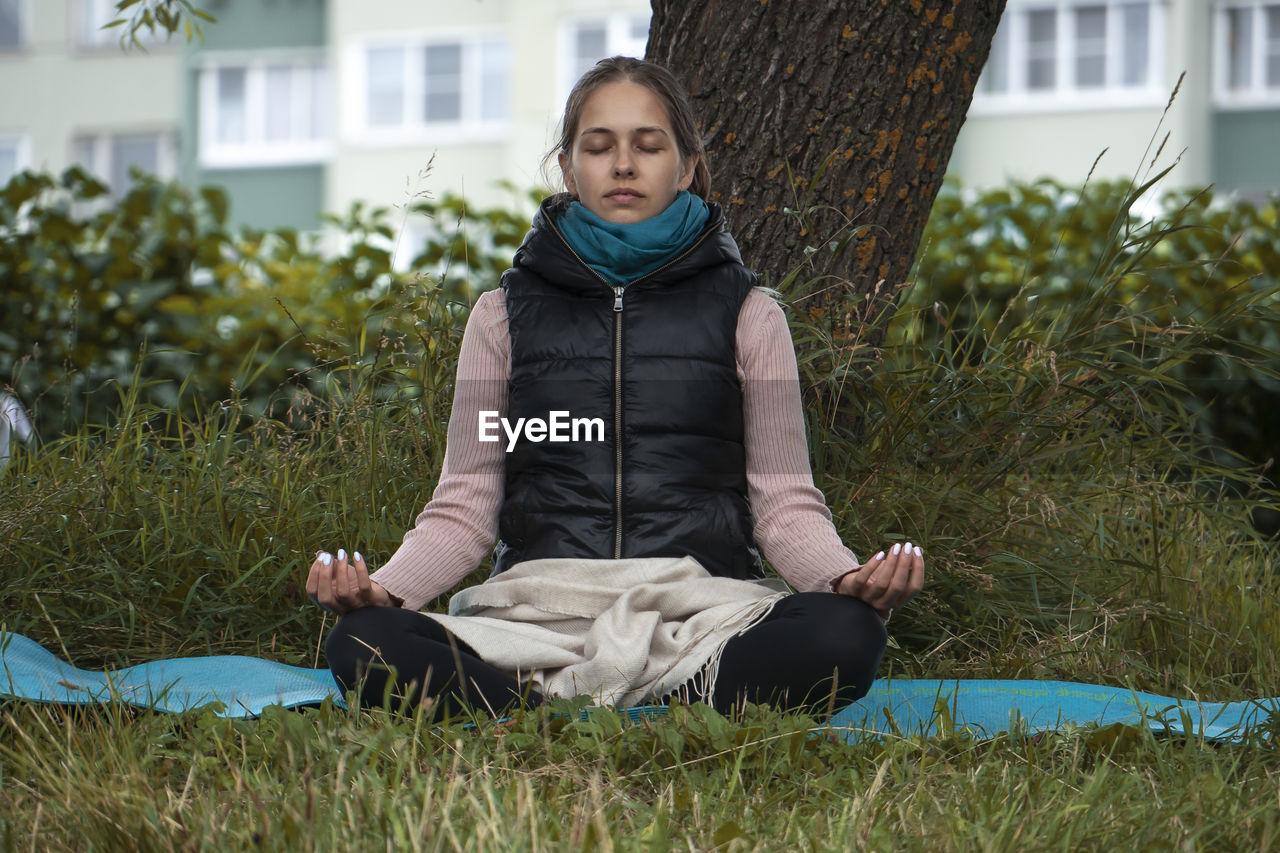FULL LENGTH OF TEENAGE GIRL SITTING ON GRASS