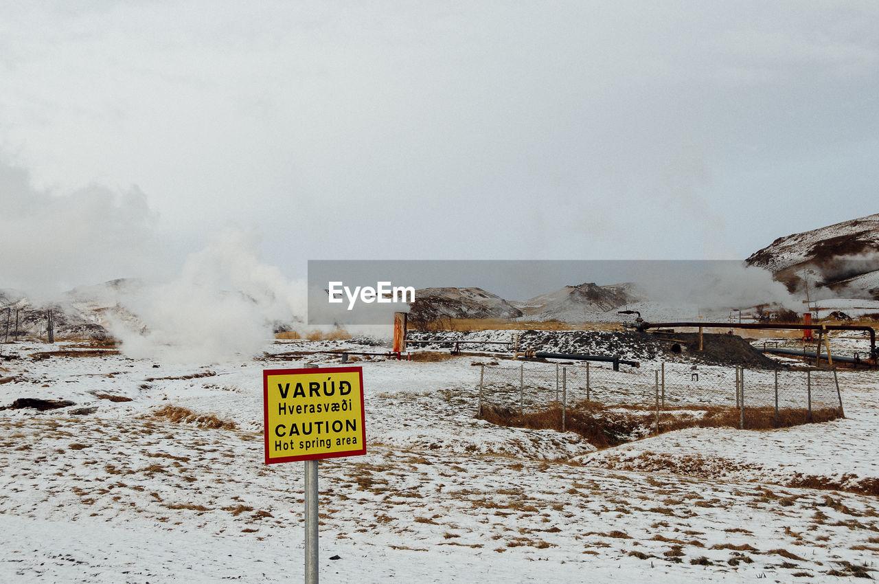 Warning sign at volcanic landscape during winter