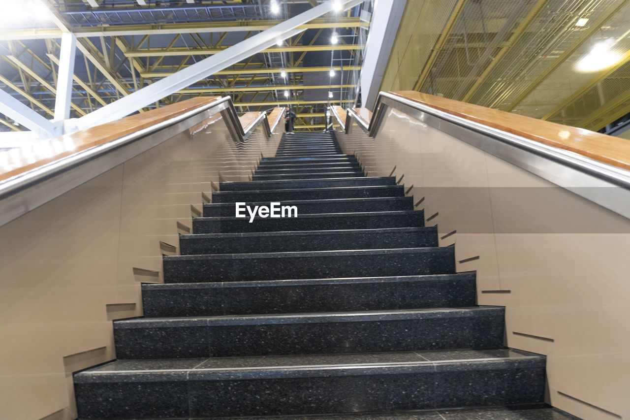 staircase, architecture, steps and staircases, railing, built structure, indoors, direction, the way forward, no people, low angle view, illuminated, building, convenience, transportation, metal, absence, day, window, ceiling