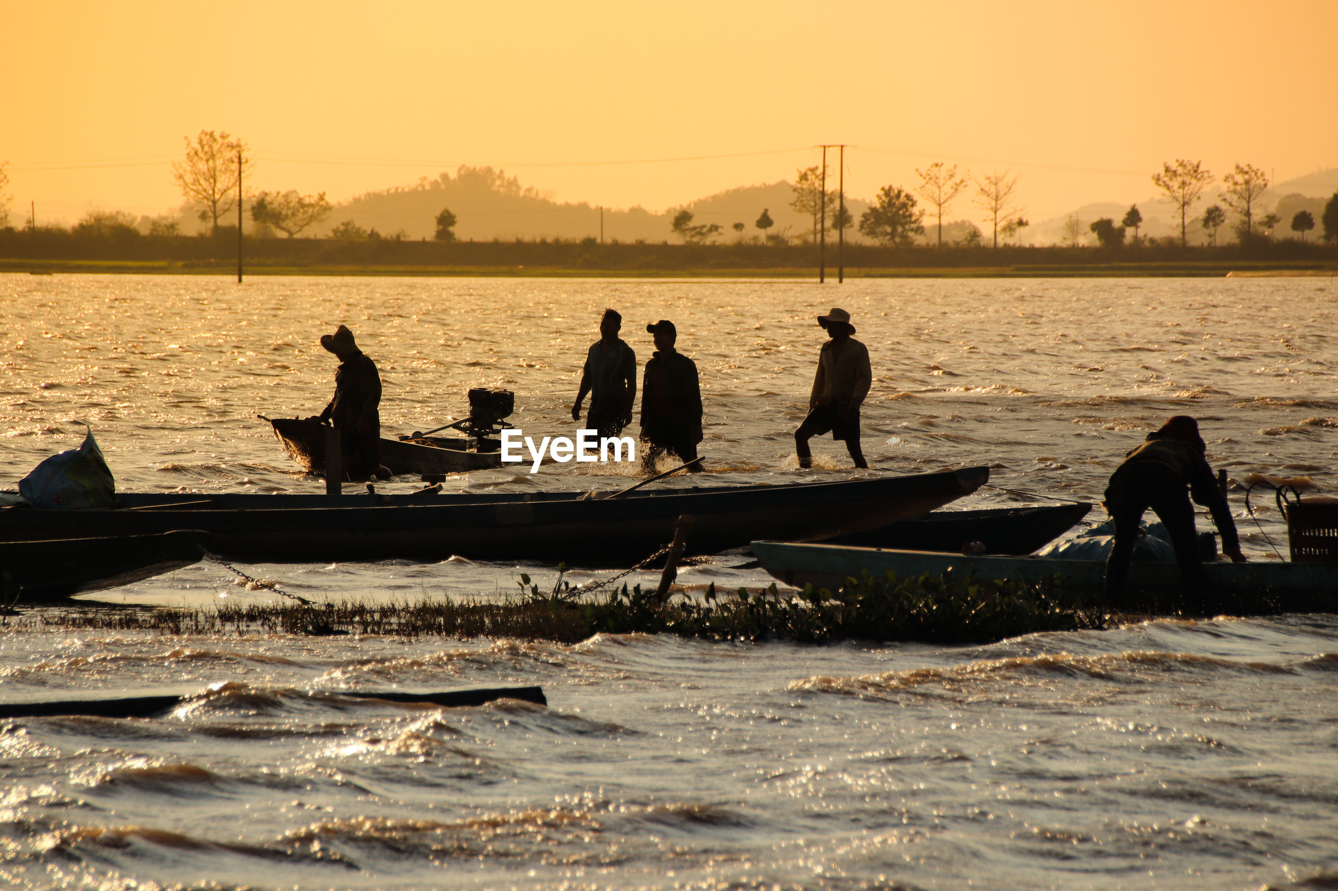 Silhouette fishermen fishing in lake against clear sky during sunset