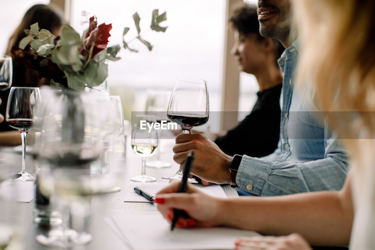 MIDSECTION OF WOMAN WITH DRINK IN RESTAURANT