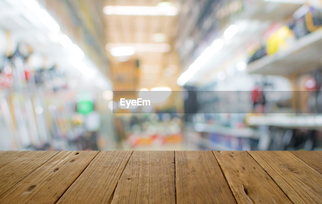 wood - material, indoors, focus on foreground, illuminated, empty, no people, table, absence, flooring, business, in a row, close-up, lighting equipment, selective focus, restaurant, bar - drink establishment, day, furniture, ceiling, wood, surface level