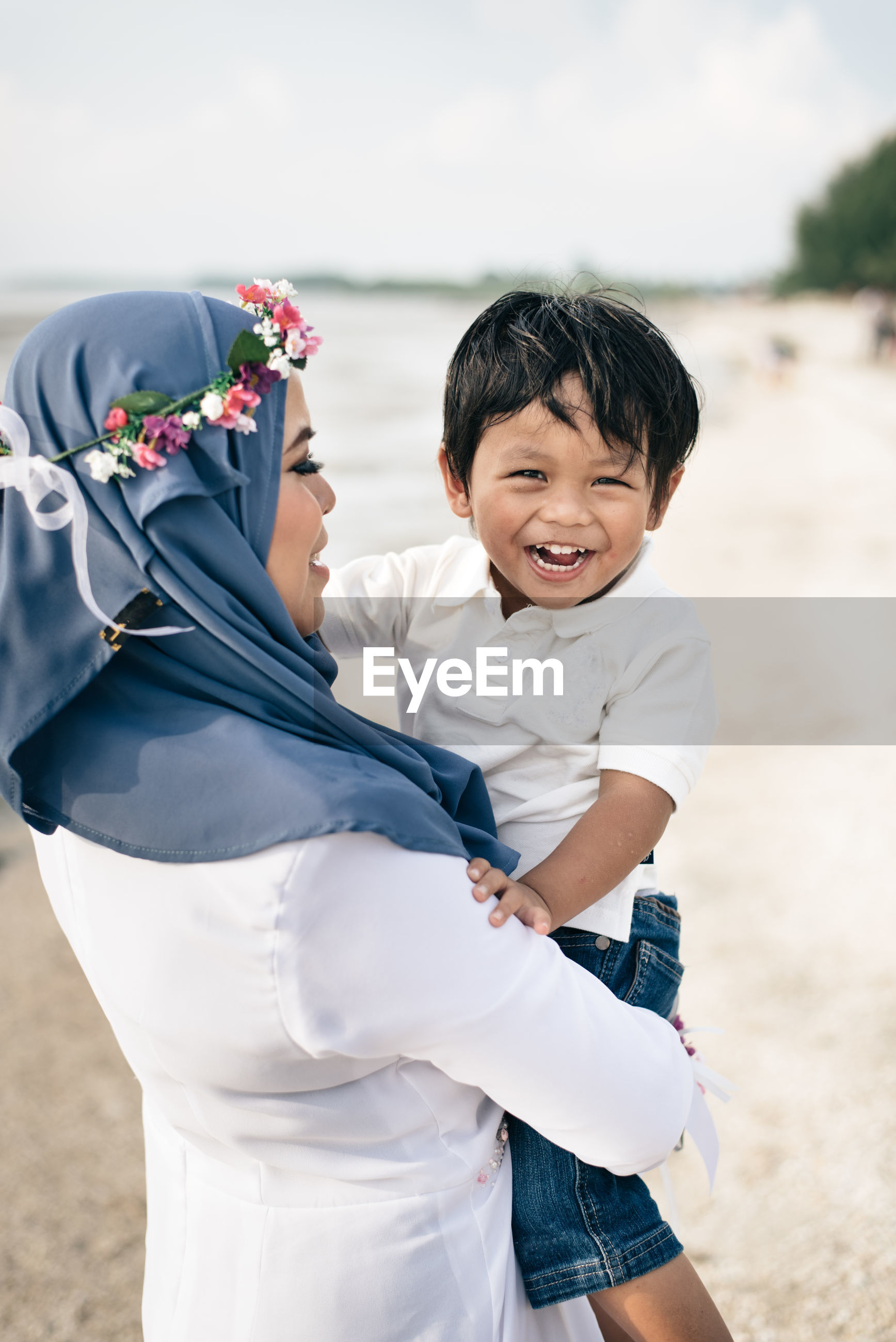 Mother carrying happy son at beach