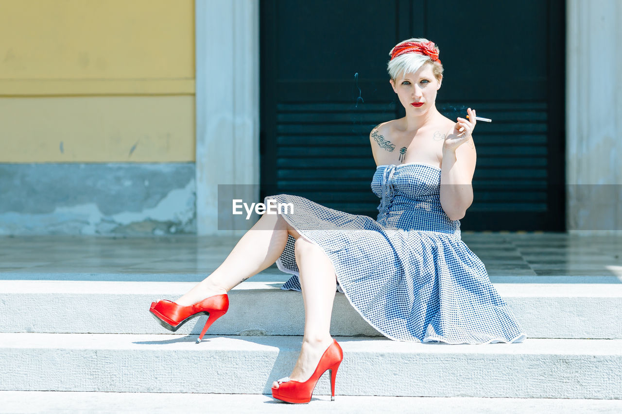 Portrait of beautiful young woman smoking while sitting on steps against building