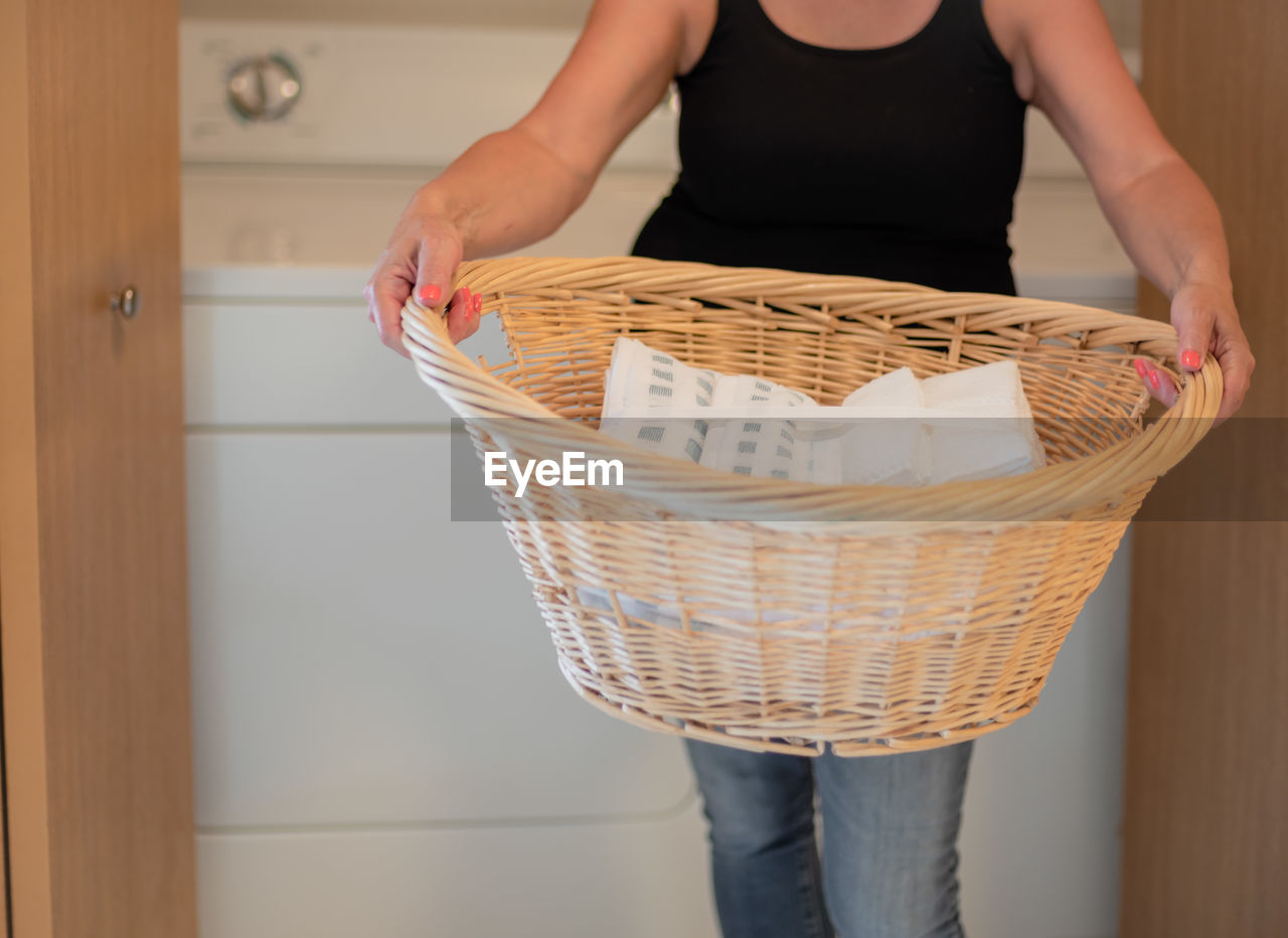 Midsection of woman holding basket at home