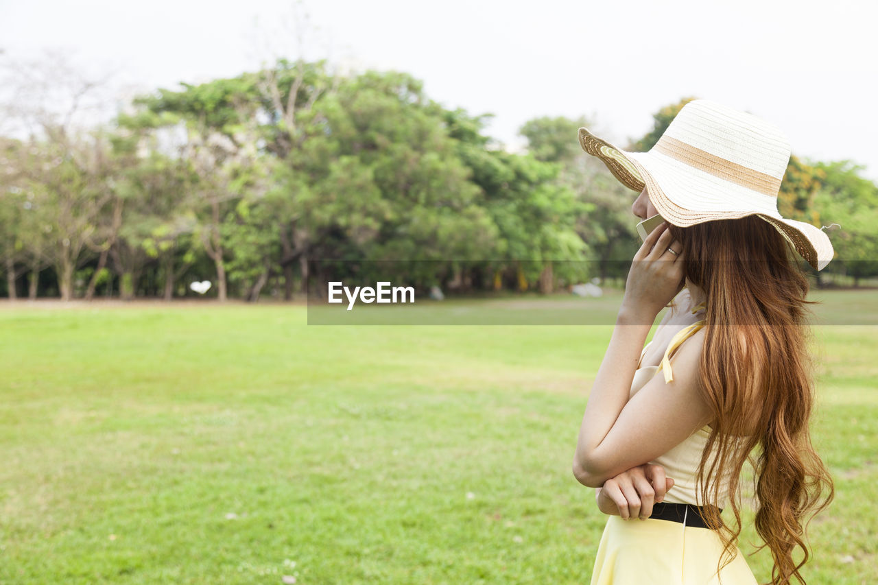 Side View Of Woman Standing On Field In Park