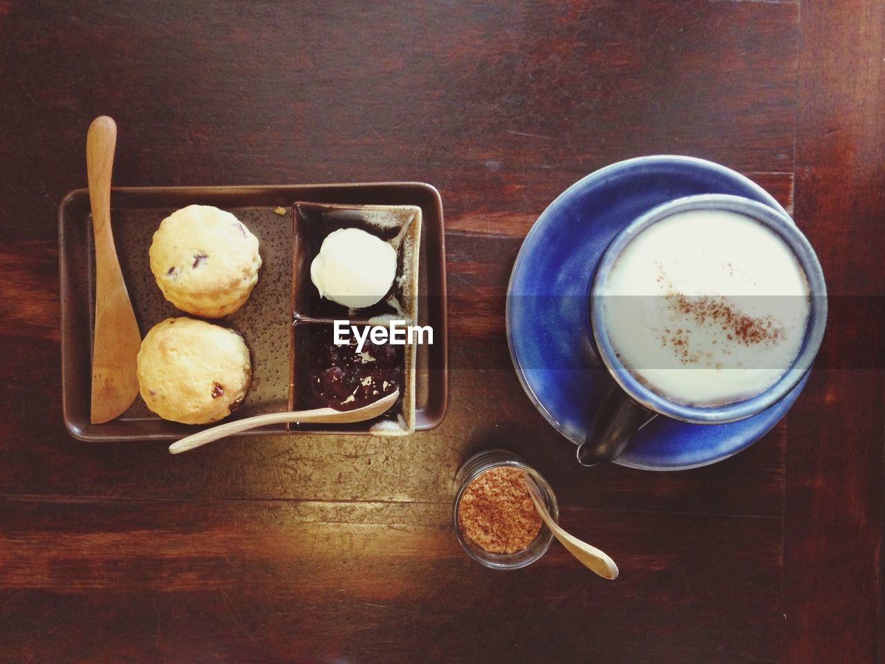 High Angle View Of Cappuccino With Scone Served On Table
