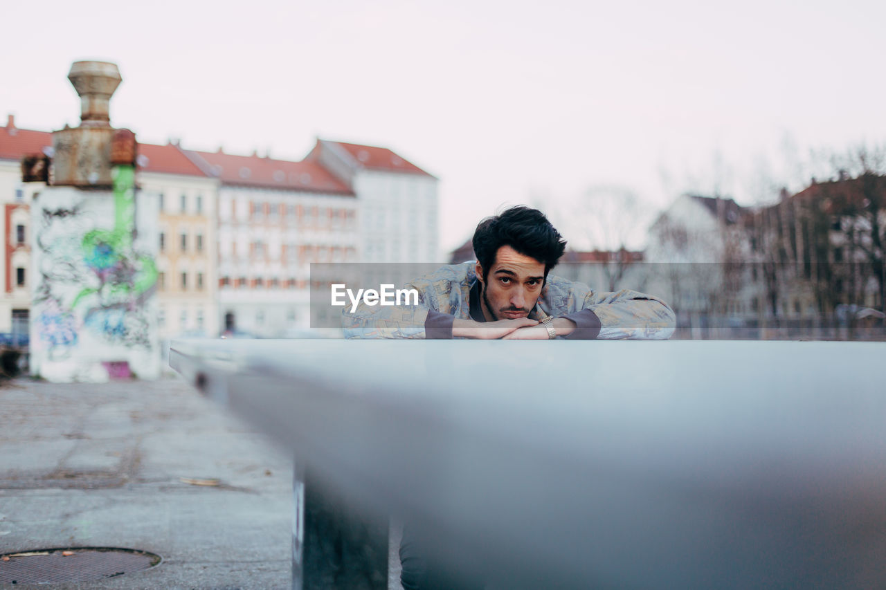 Portrait Of Young Man Leaning On Railing Against Sky In City