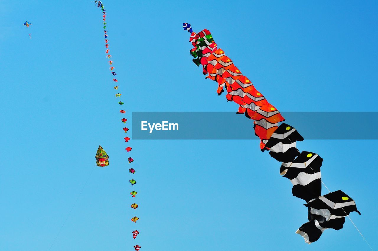 sky, multi colored, low angle view, clear sky, blue, decoration, nature, no people, celebration, day, art and craft, creativity, hanging, outdoors, red, in a row, shape, design, flying, festival