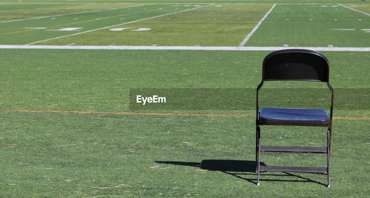 Empty chair on playing field during sunny day