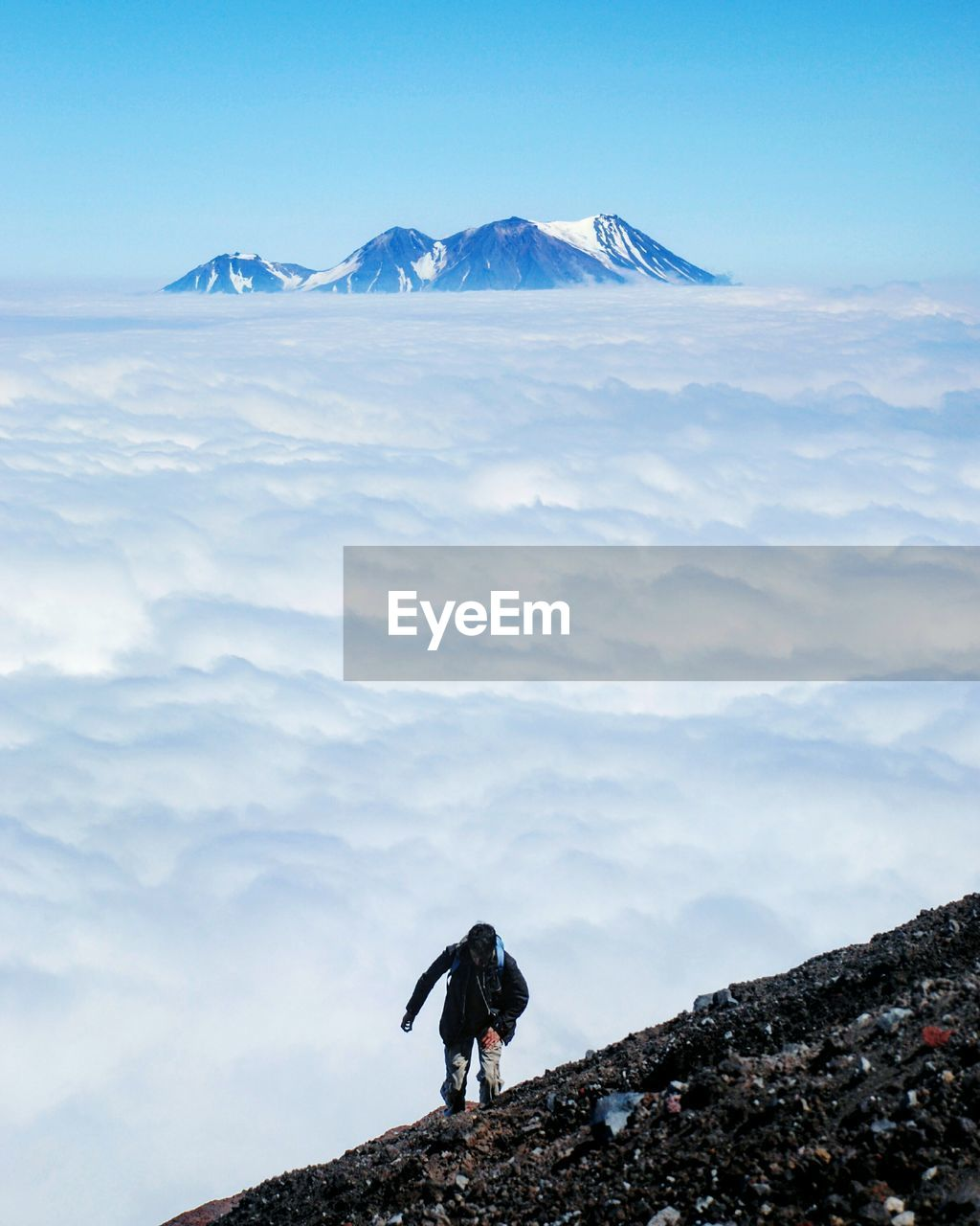 High Angle View Of Man Climbing Mountain Against Cloudy Sky