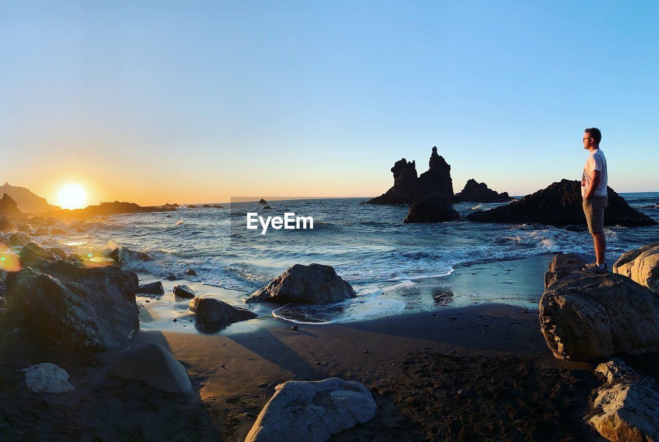 Side view of young man standing on rock formation at beach during sunset