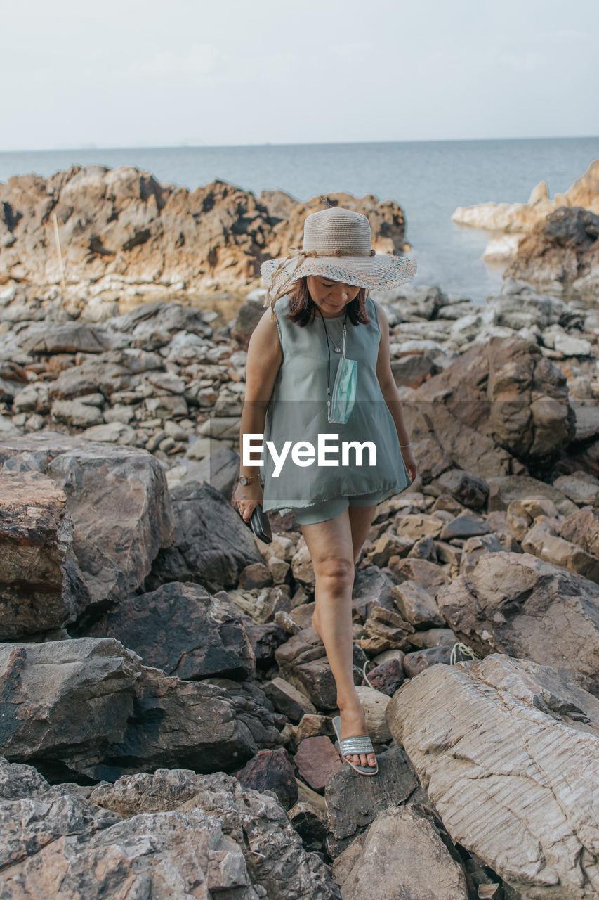 Beautiful woman walking on rock over sea