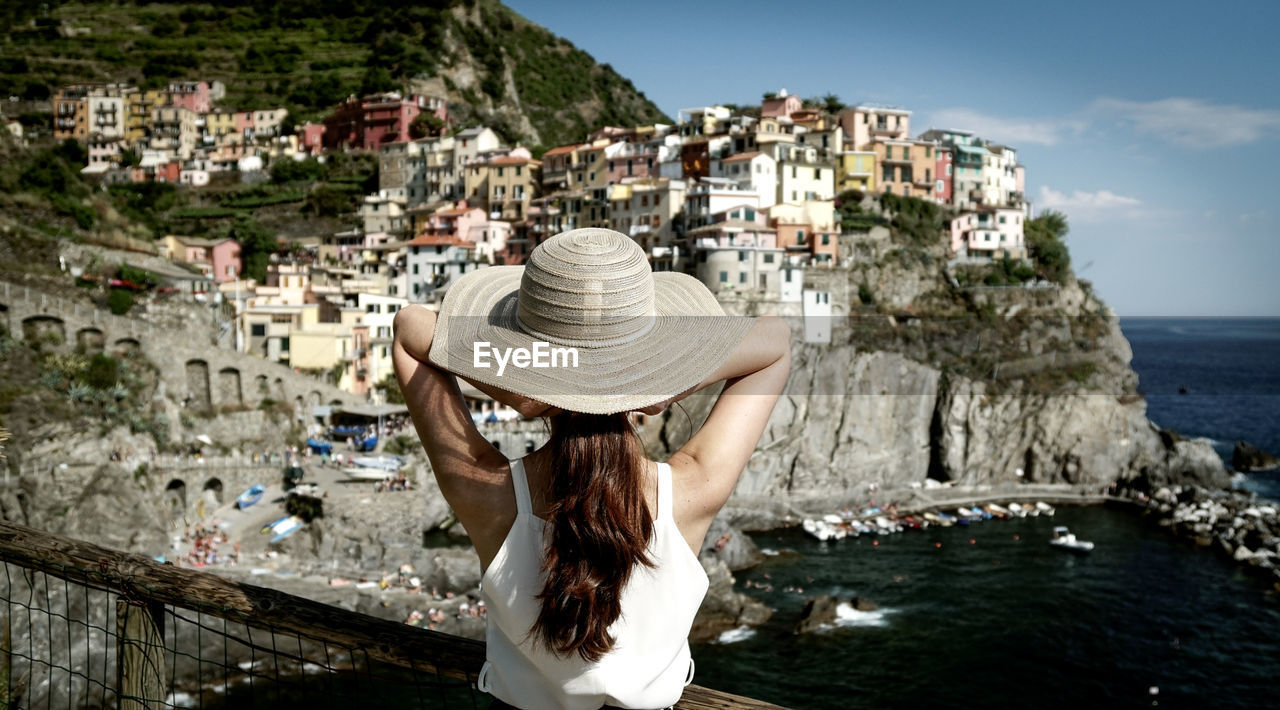Rear View Of Woman Standing Against Buildings At Vernazza
