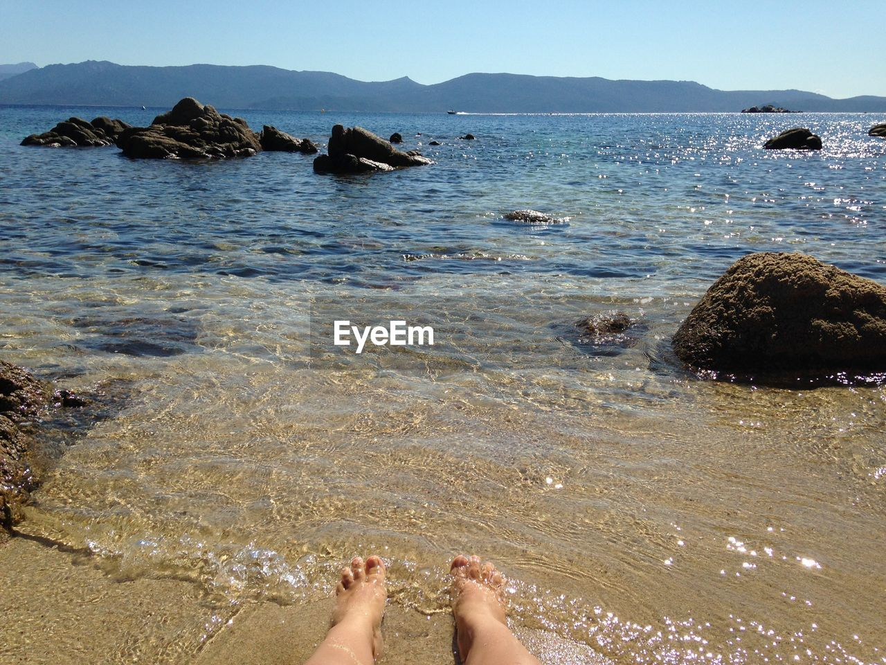 water, low section, human leg, body part, human body part, sea, real people, land, barefoot, nature, one person, beach, day, human foot, personal perspective, lifestyles, sunlight, leisure activity, rock, outdoors