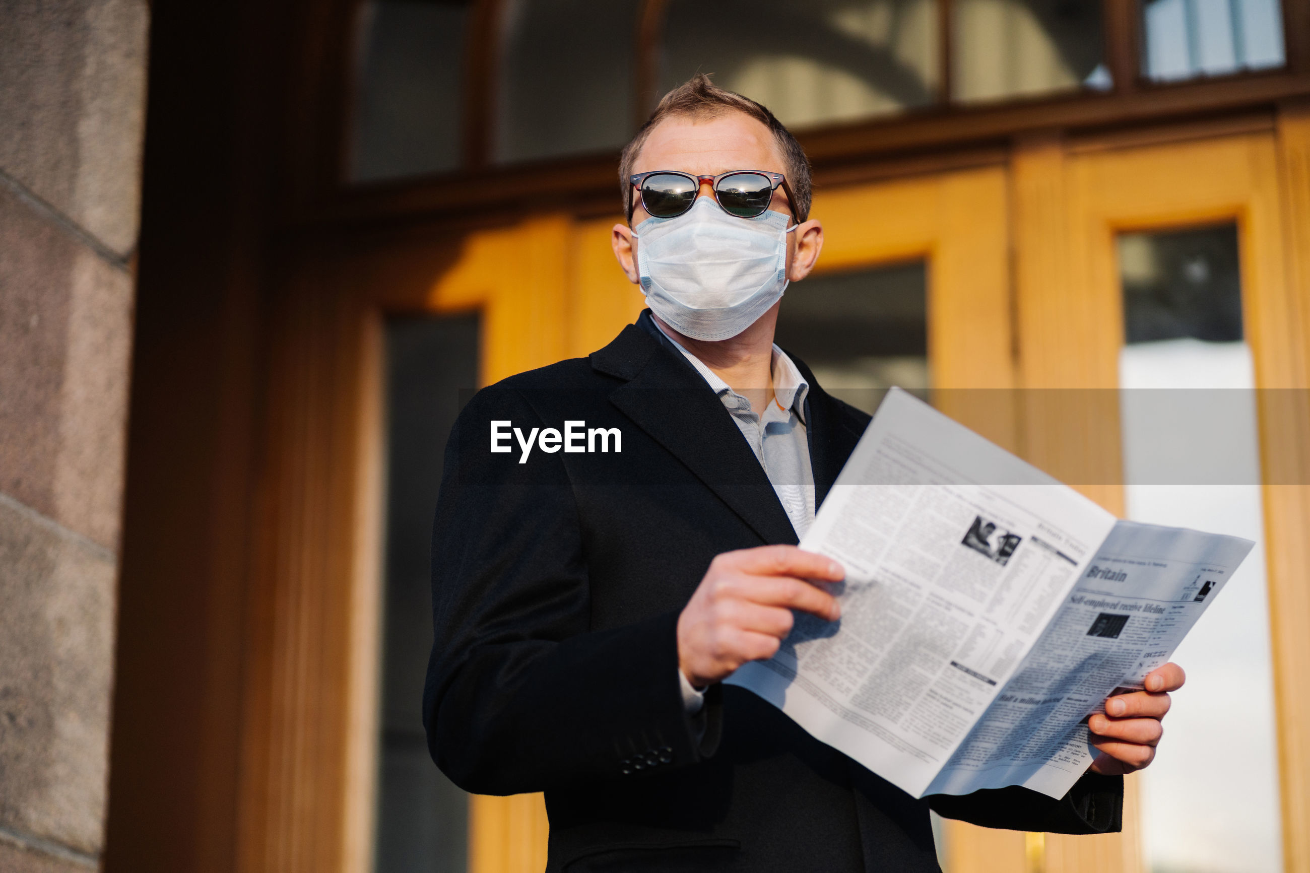 Businessman wearing mask while standing with newspaper in city