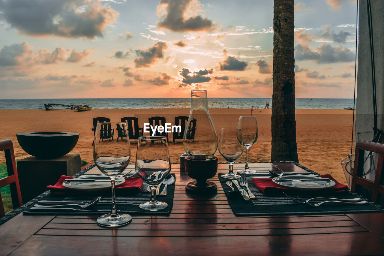 Place setting on table against beach