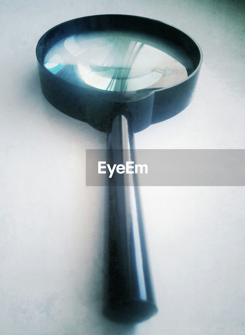 Close-up of magnifying glass against white background