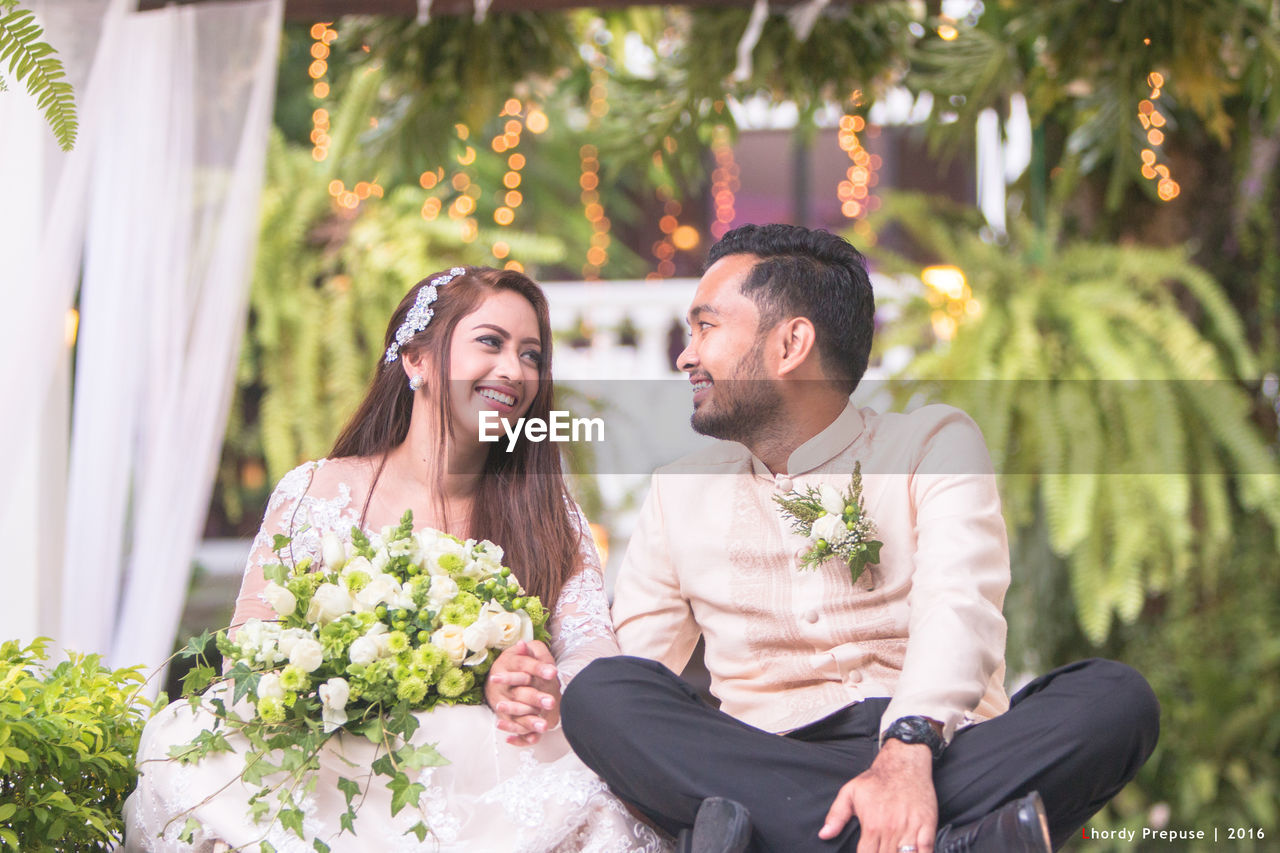 flower, love, togetherness, happiness, wedding, two people, smiling, young adult, young women, outdoors, bride, celebration, couple - relationship, wedding dress, sitting, day, cheerful, women, bonding, bridegroom, people