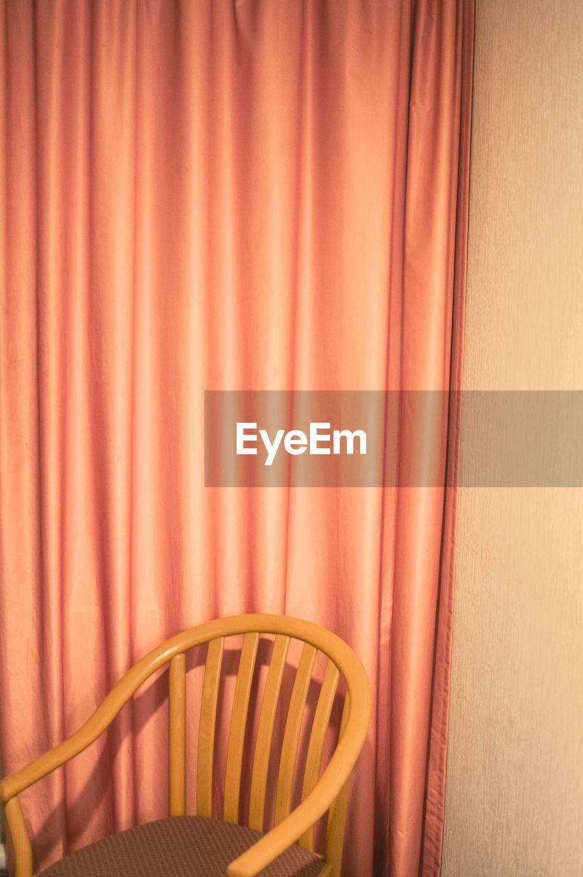 Empty Chair Against Curtain
