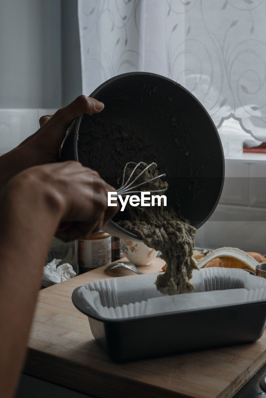 Cropped hands serving food in bowl on table at home