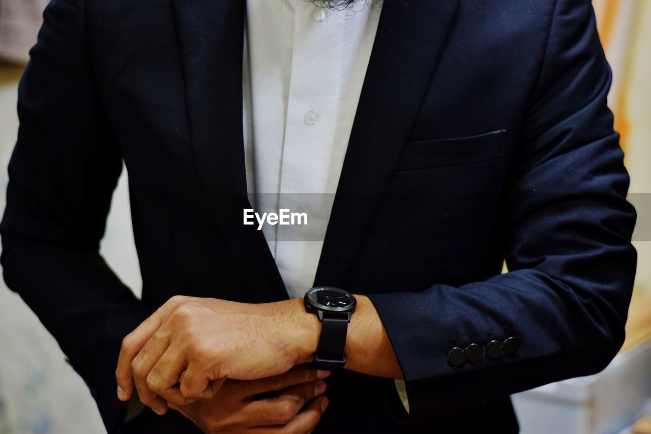 midsection, men, one person, hand, wristwatch, watch, real people, front view, time, standing, human hand, well-dressed, business, clothing, adult, business person, occupation, suit, businessman, checking the time