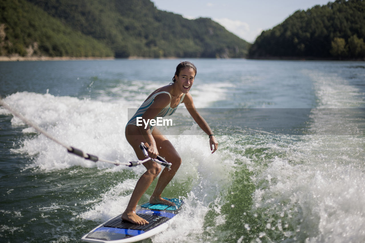 Girl surfing in lake against mountains