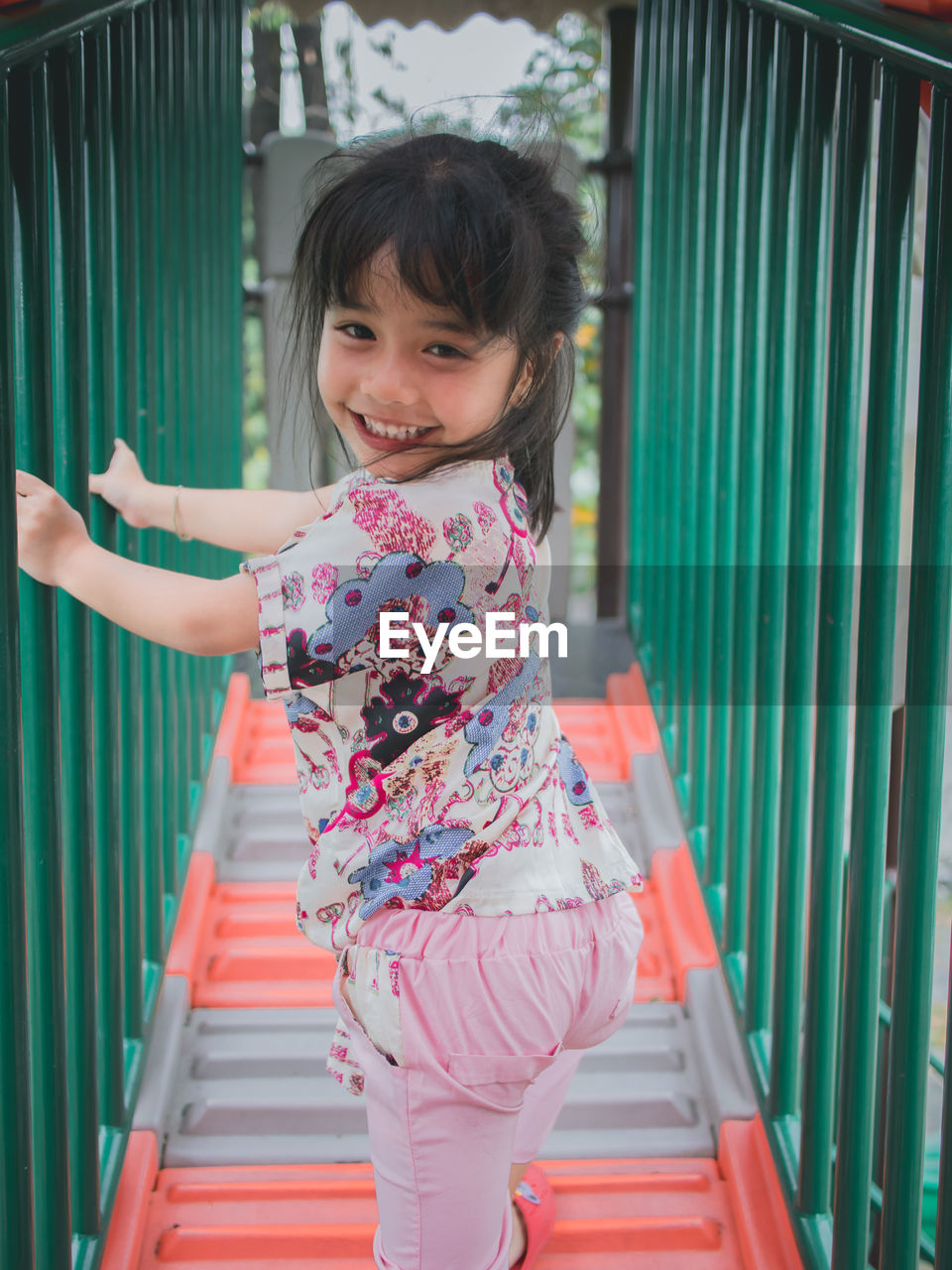 child, childhood, real people, portrait, girls, one person, women, looking at camera, females, smiling, happiness, casual clothing, lifestyles, railing, three quarter length, staircase, architecture, leisure activity, innocence, outdoors, hairstyle, human arm