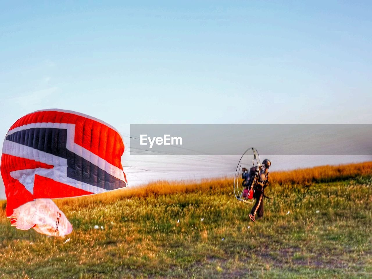 Man with powered parachute on grassy field against clear sky during sunset