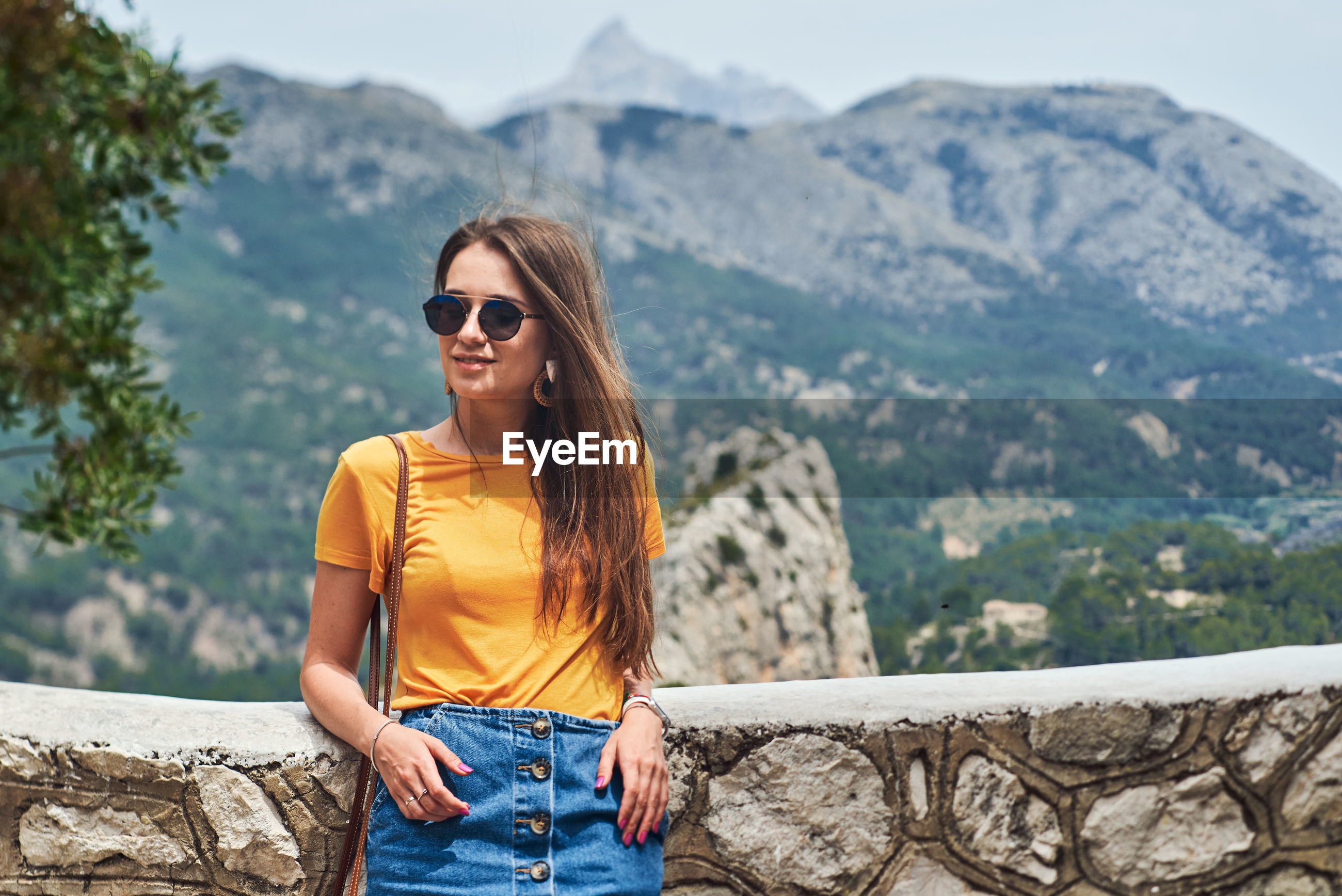 YOUNG WOMAN IN SUNGLASSES ON RETAINING WALL