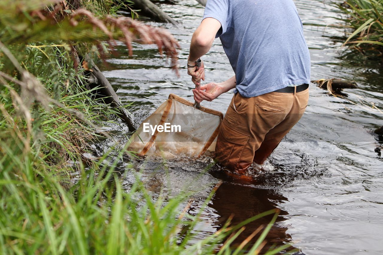 REAR VIEW OF MAN WORKING IN WATER