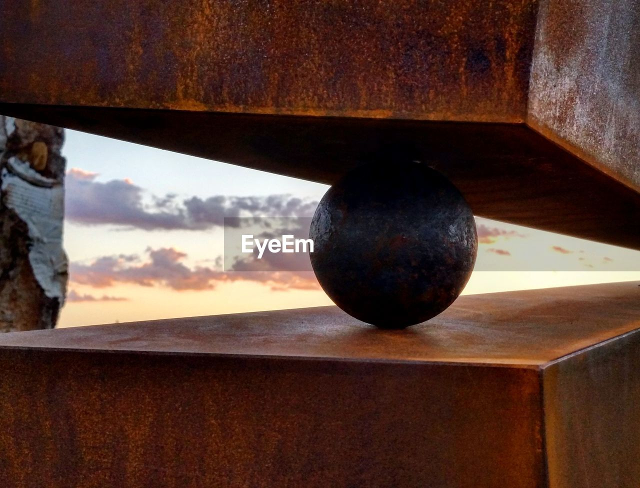 sphere, no people, close-up, cloud - sky, sky, indoors, nature, shape, metal, wood - material, geometric shape, rusty, focus on foreground, day, sunset, design, ball, still life, transparent