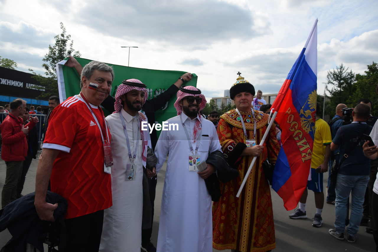 group of people, real people, men, day, crowd, flag, traditional clothing, people, adult, women, standing, lifestyles, celebration, patriotism, cloud - sky, arts culture and entertainment, leisure activity, outdoors