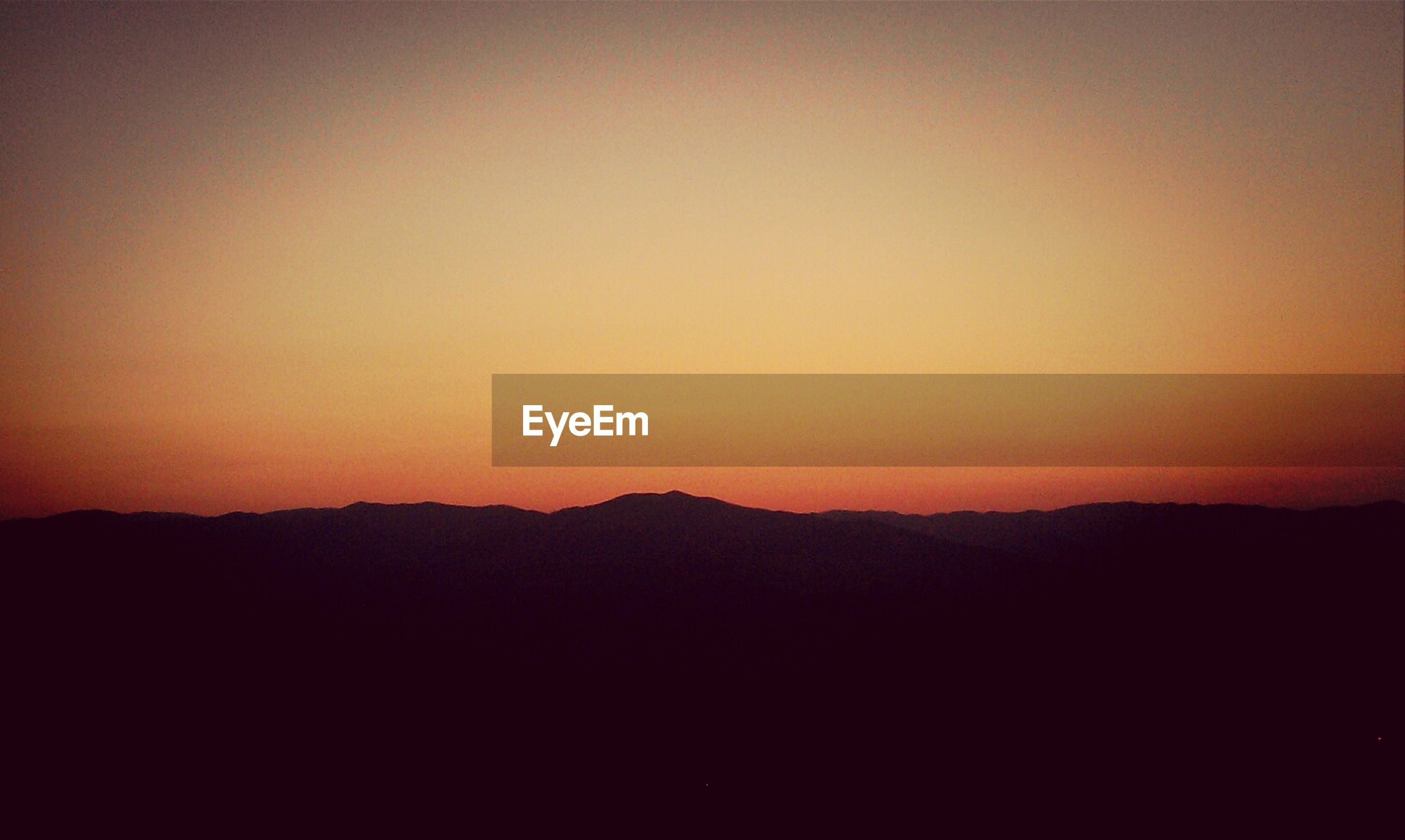 sunset, copy space, silhouette, scenics, tranquil scene, tranquility, beauty in nature, mountain, clear sky, orange color, nature, idyllic, landscape, mountain range, dark, dusk, sky, outdoors, non-urban scene, outline