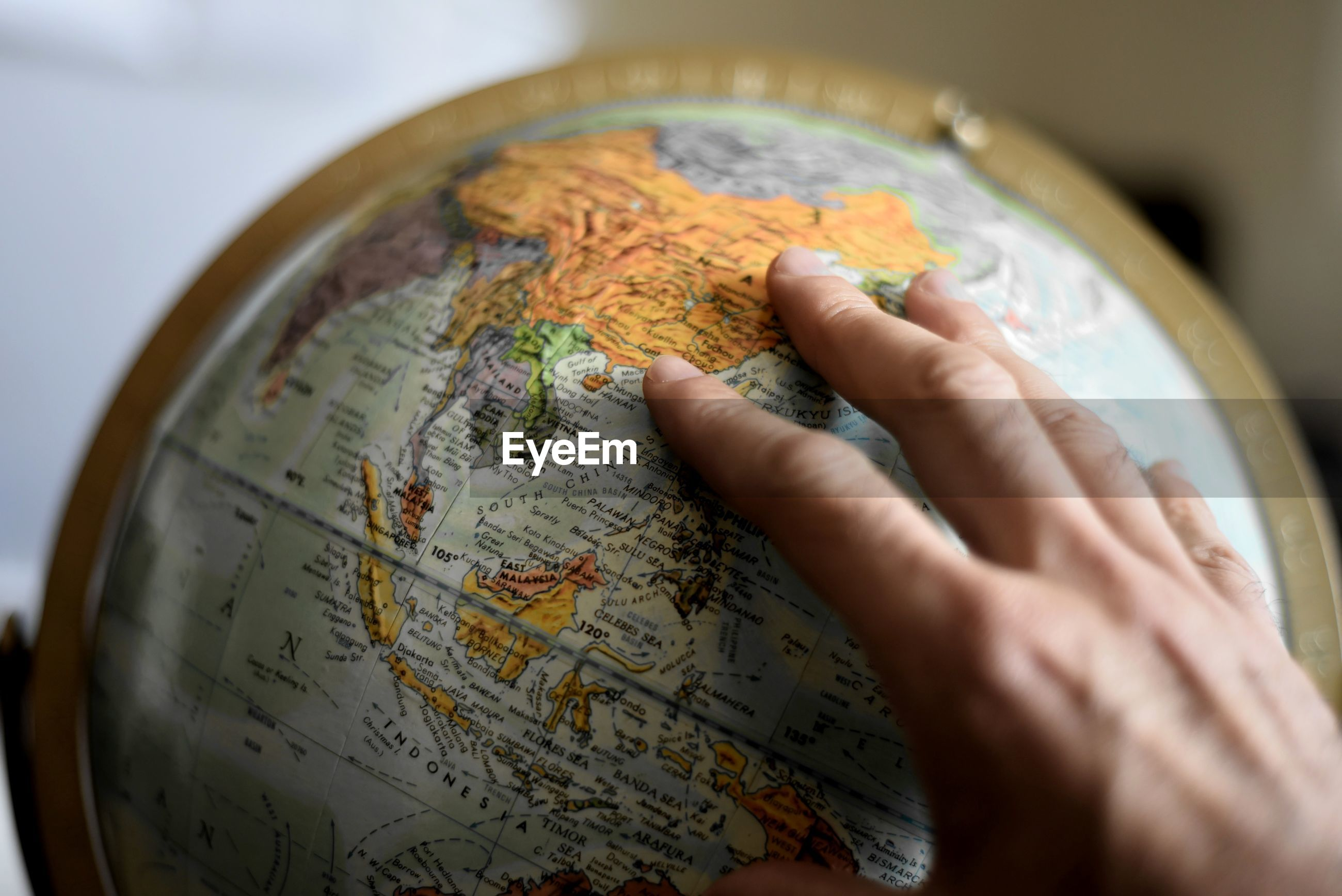 Cropped image of hand touching globe