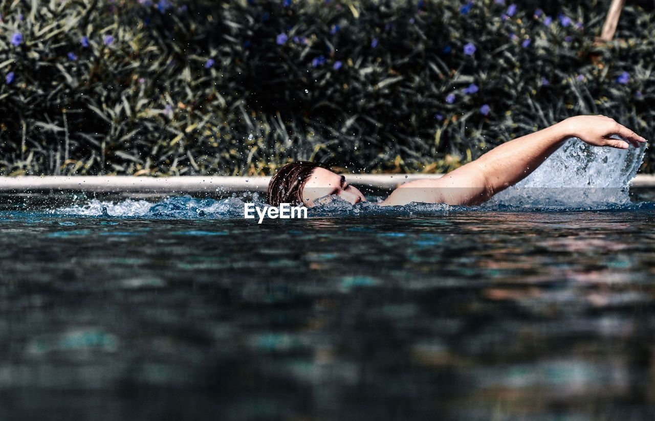 one person, lying down, selective focus, day, relaxation, young adult, nature, water, headshot, leisure activity, adult, portrait, lifestyles, waterfront, real people, outdoors, surface level, human arm