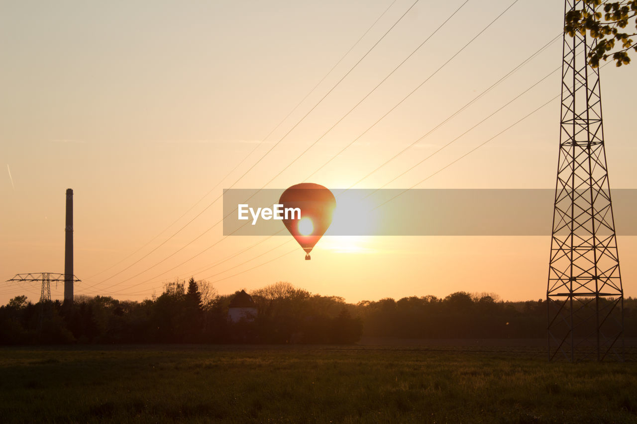 sunset, sky, orange color, electricity pylon, nature, sun, cable, electricity, field, power line, power supply, no people, environment, fuel and power generation, land, landscape, plant, outdoors, silhouette, technology