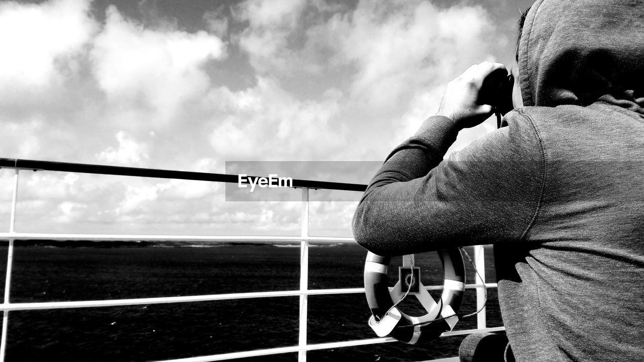 one person, real people, sky, leisure activity, men, water, holding, activity, lifestyles, nature, day, photography themes, cloud - sky, photographing, railing, sea, outdoors, camera - photographic equipment, hand, digital camera