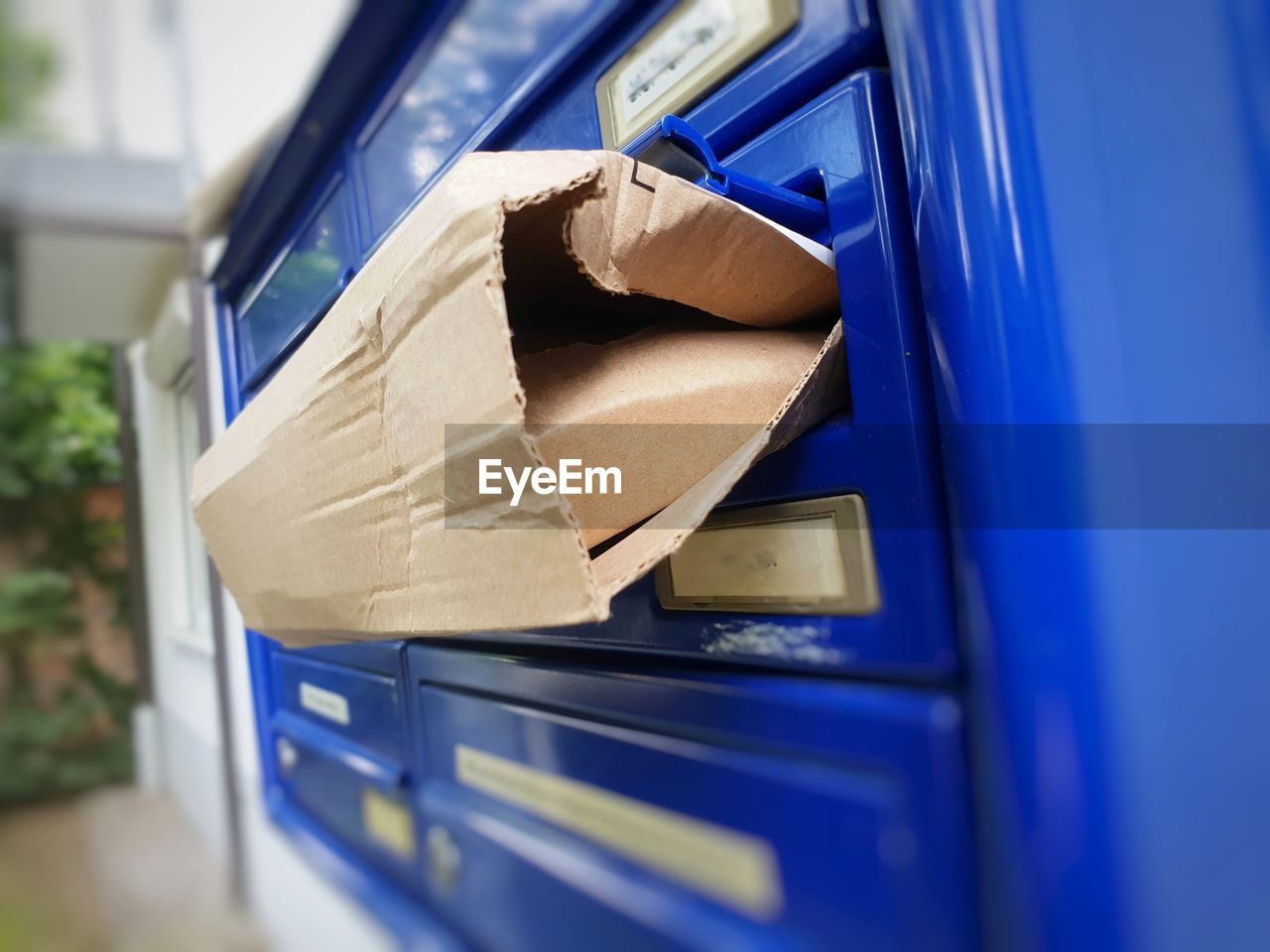Close-up of cardboard on blue mailbox