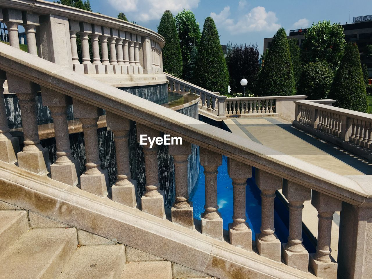 architecture, built structure, tree, railing, building exterior, nature, day, staircase, plant, no people, steps and staircases, balustrade, sunlight, architectural column, connection, outdoors, building, bridge, water, sky