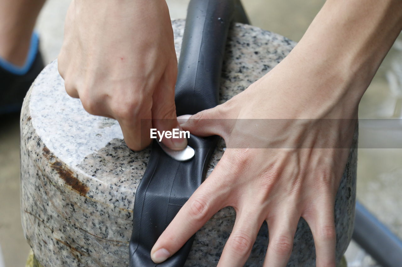 Close-Up Of Person Hand Repairing Bicycle Tube