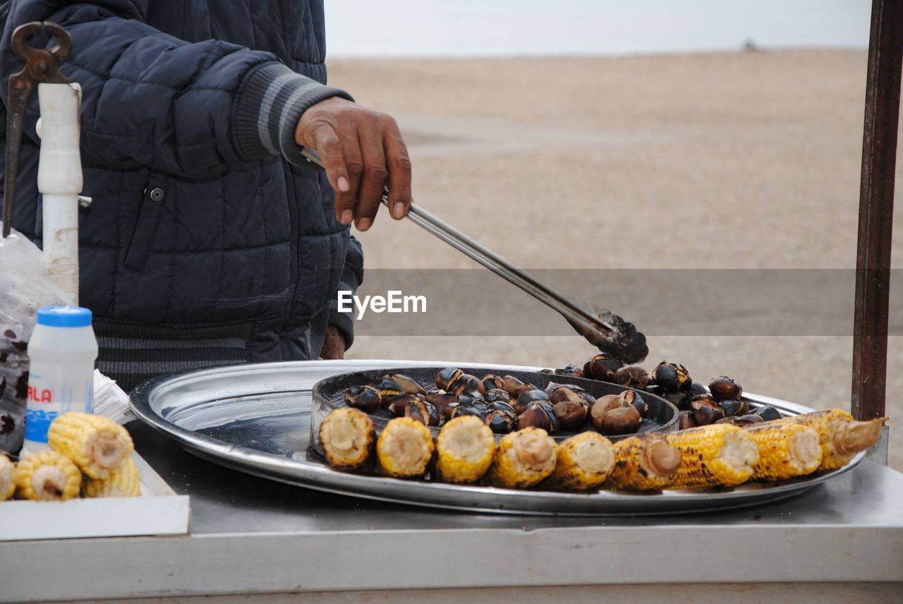 Midsection Of Vendor Holding Serving Tongs By Food At Market Stall